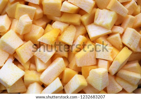 uncooked cube size pieces of chopped winter squash, orange in color. Perfect for background pictures for pumpkin pie and other Fall recipes.
