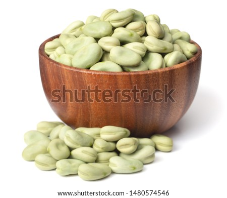uncooked dried green faba beans in the wooden bowl, isolated on white background