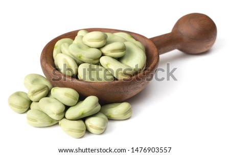 uncooked dried green faba beans in the wooden spoon, isolated on white background