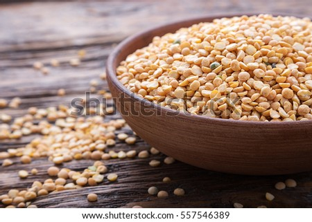uncooked dried peas in an earthenware dish on a wooden surface, next to scattered peas #557546389