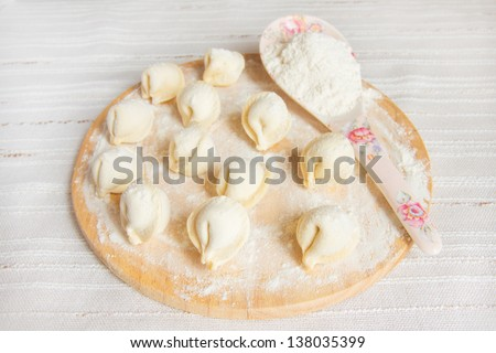 Uncooked dumplings (russian traditional food - pelmeni) on wooden cuting board with flour over linen background.