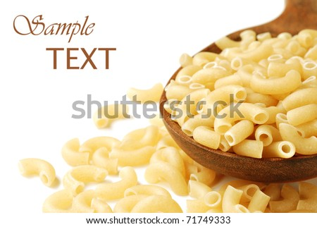 Uncooked elbow macaroni spilling from wooden spoon on white background with copy space.  Macro with shallow dof.