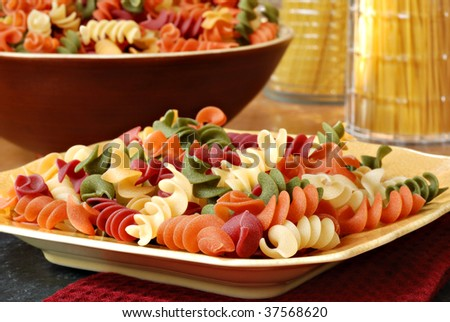 Uncooked five color pasta on plate with containers of pasta in background.  Natural side lighting emphasizes detail and textures.  Macro with shallow dof.
