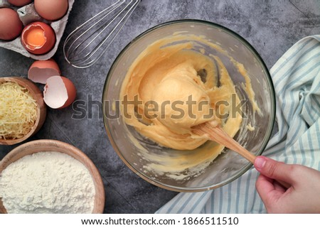 Uncooked French chou pastry dough and hands batting with paddle in a mixing bowl. Preparation step of traditional French gougères with ingredients such flour ,butter ,grate cheese, eggs.  Foto stock ©