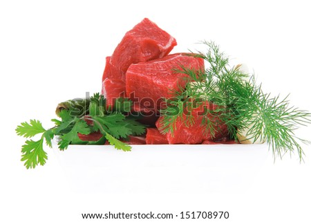 uncooked fresh beef meat chunks on white bowls with green hot peppers and vegetables isolated over white background