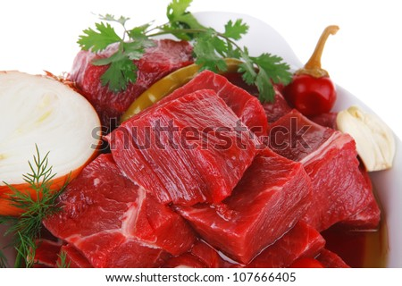 uncooked fresh beef meat chunks on white bowls with vegetables and red peppers isolated over white background