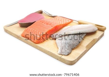 uncooked fresh sole , salmon , and red tuna fish pieces served over wooden board isolated on white background