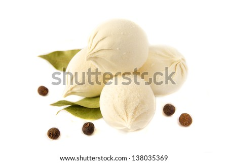 Uncooked frozen dumplings (russian traditional food - pelmeni, khinkali) with pepper and bay leaf isolated on white background close up.