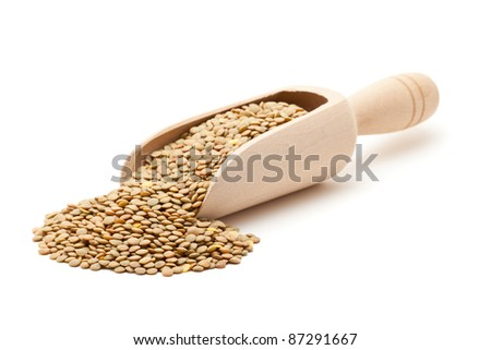 Uncooked lentils in wooden scoop over white background