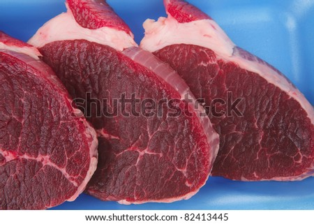 uncooked meat : raw fresh beef pork tenderloin strip ready to cooking on blue tray isolated over white background - stock photo