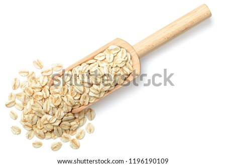 uncooked oatmeal in the wooden spoon, isolated on white, top view