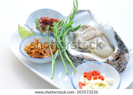 Uncooked oyster on restaurant eat with side dish