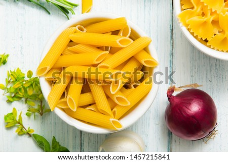 uncooked pasta variations and fresh spices on white wood table, top view #1457215841