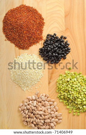 Uncooked quinoa, black beans, pinto beans, and split peas on a cutting board