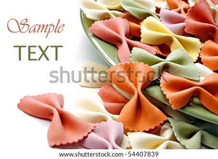 Uncooked rainbow farfalle pasta spilling from plate on white background with copy space.  Macro with shallow dof.