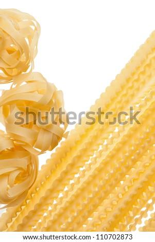 Uncooked raw mafalde and tagliatelle pasta.