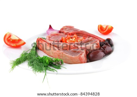 uncooked ribs on white with greenery and tomatoes - stock photo
