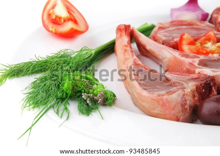 uncooked ribs on white with greenery and tomatoes