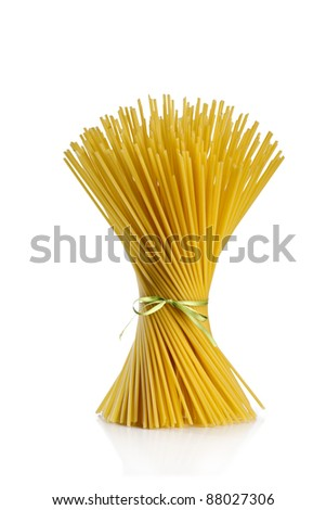 uncooked spaghetti tied with green ribbon on white background