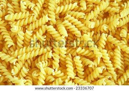 Uncooked spiral Italian pasta background. - stock photo