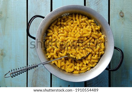 Uncooked spiral pasta in a strainer with metal spoon, on a light blue backdrop. Top view.  Stock photo ©