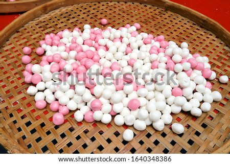 """Uncooked """"Tang Yuan"""", delicious red and white rice dumpling balls, in a bamboo plate. Asian traditional food for Chinese Winter Solstice Festival and Lantern Festival."""