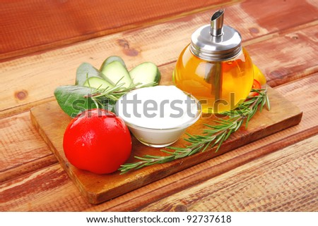 uncooked vegetables with olive oil over wooden table