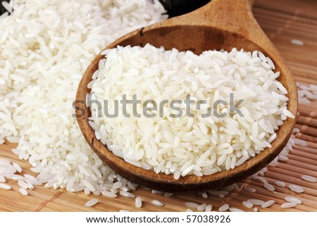 Uncooked white rice in a wooden spoon. Shallow DOF.