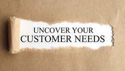uncover your customer needs. Text on white paper on torn paper