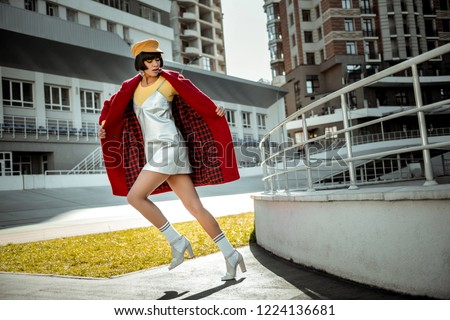 Uncovering red coat . Beautiful dark-haired woman unrealistically stepping with her white shoes removing her overcoat