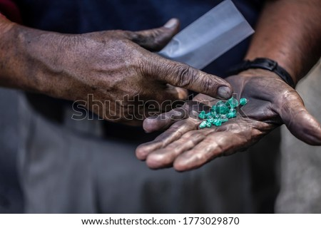 Uncut emeralds in the hand of a Colombian emerald miner in Muzo, Colombia.