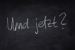 und jetzt translates as what now in German - handwritten question on chalkboard - uncertainty, angst and anxiety about the future concept