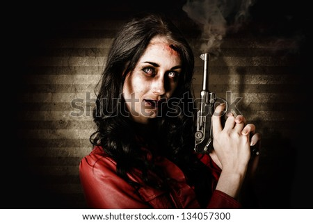 Undead female zombie glaring at you while holding a smoking gun in a kill or be killed concept on striped interior background