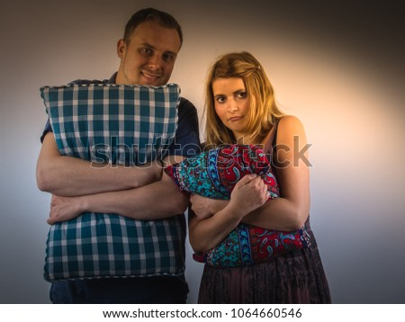 Undecided unsure young couple standing in the space in the dark and hugging their pillows. #1064660546