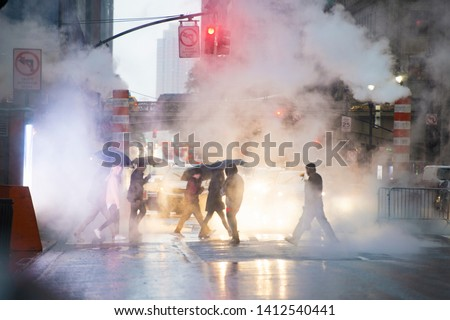 Undefined people with umbrellas are crossing the 42nd street in Manhattan. Steam coming out from from the manholes in the background. Manhattan, New York City, Usa. stock photo