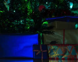 Under a Christmas tree decorated and illuminated with green lights, you can see a lot of gifts with ribbons and wrapped with different colored papers and drawings