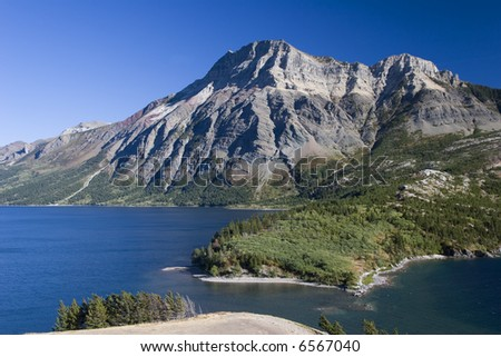 Under a clear blue sky on a sunny day, a mountain flanks where Upper and Lower Waterton Lakes join.