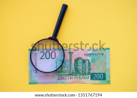 Under a magnifying glass looking at a 200-ruble banknote for authenticity. #1351767194