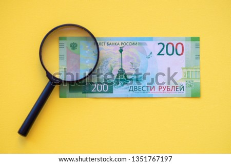 Under a magnifying glass looking at a 200-ruble banknote for authenticity. #1351767197