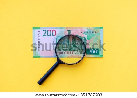 Under a magnifying glass looking at a 200-ruble banknote for authenticity. #1351767203