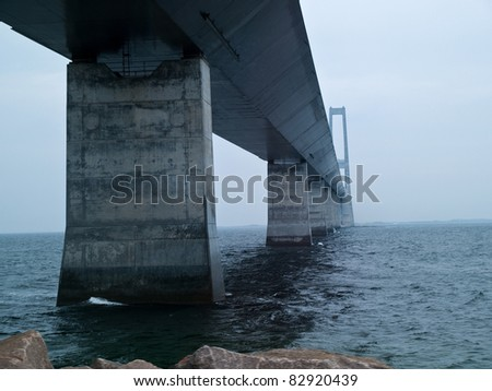 Under a massive modern design concrete bridge support over water