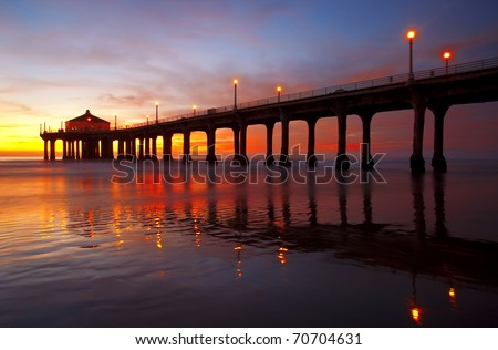 Under a spectacular sunset, Manhattan Beach Pier reflected in the Pacific Ocean - Los Angeles, California.
