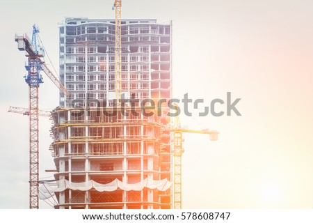 Under construction high-rise building with yellow construction crane in the sunlight stock photo