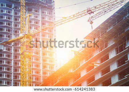 Under construction high-rise building with yellow construction crane in the sunlight