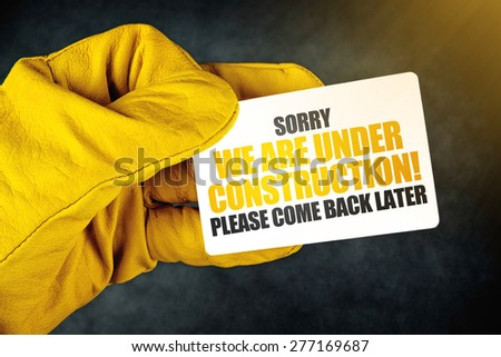 Under Construction on Business Card, Male Hand in Yellow Leather Construction Working Protective Gloves Holding Card with Rounded Corners.