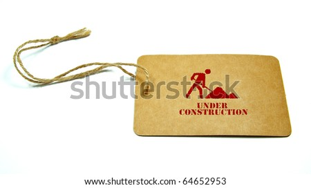 "under construction sign and ""under construction"" written on a tag tied with a brown string isolated on a white background"