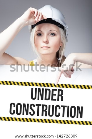 Under construction sign on template board with worker woman