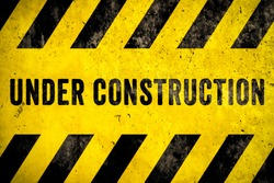 Under construction warning sign text with yellow black stripes painted over concrete wall cement facade texture background. Concept for do not enter the area, caution, danger, construction site