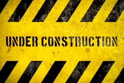 Under construction warning sign text with yellow black stripes painted over concrete wall coarse facade as texture background. Concept for do not enter the area, caution, danger, construction site.