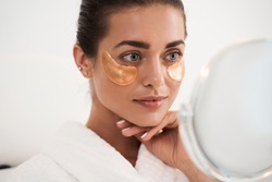 Under eye masks for puffiness, wrinkles, dark circles. Eye patches concept. Satisfied woman in white bathrobe applying gold eye patches in bathroom while looking at the mirror